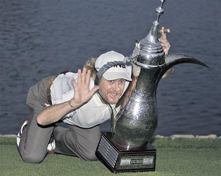 Spain's Miguel Angel Jimenez poses with his Dubai Desert Classic trophy