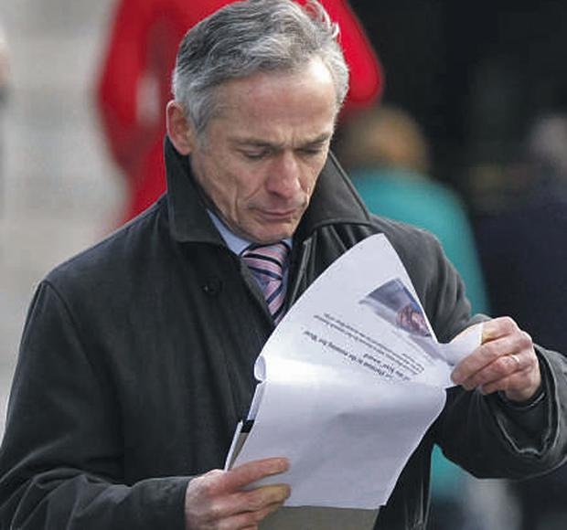 Richard Bruton pictured reading his notes outside Leinster House