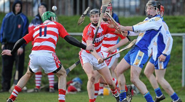 Padraig Phelan's hurley breaks as he comes under pressure from Cork IT's Brian Corry (No 11) and Lorcan McLoughlin at Mobhi Road. PAT MURPHY / SPORTSFILE
