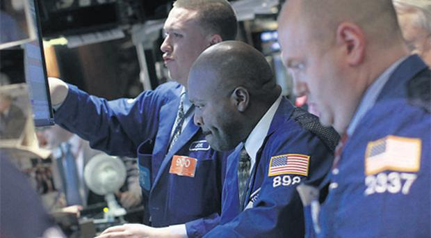 Traders working on the floor at the New York Stock Exchange, yesterday