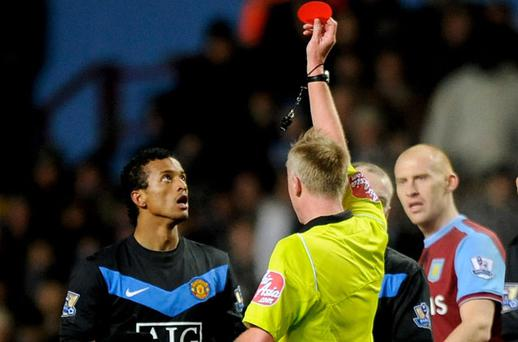 Referee Peter Walton shows the red card to Nani after his two-footed lunge at Stiliyan Petrov at Villa Park last night Photo: Getty Images