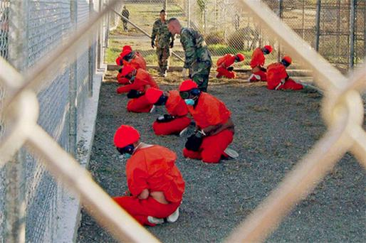 In this file image, detainees kneel in a holding area, at Camp X-Ray in Guantanamo Bay, Cuba. Following the failed attack in Detroit last Christmas, the wannabe-murderer named Guantanamo as the reason he signed up for the jihad
