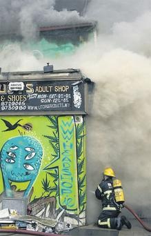 A firefighter hosing down the fire yesterday at the Nirvana head shop and Utopia sex shop in Dublin, which sent clouds of smoke billowing down Capel Street.