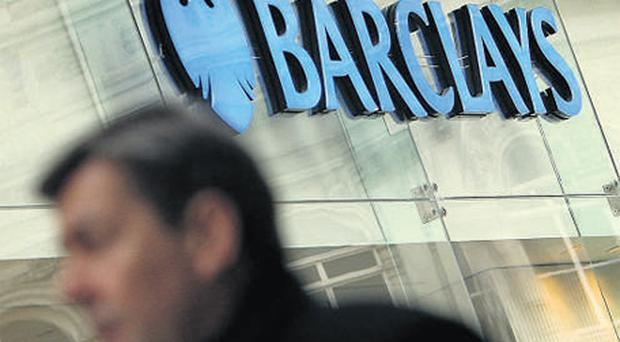 A man walks past a branch of Barclays in central London. The British banking giant said yesterday it had reined in payouts, with its two top executives refusing cash bonuses
