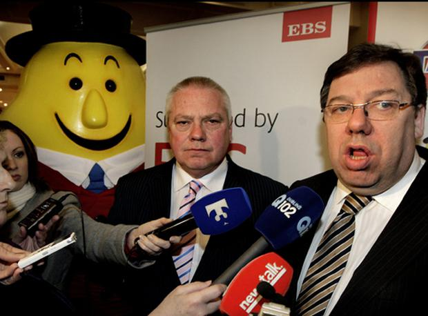 Paidi O Se listens to Brian Cowen speak to the media at the launch last night as Mr Tayto lurks in the background. Photo: Steve Humphreys