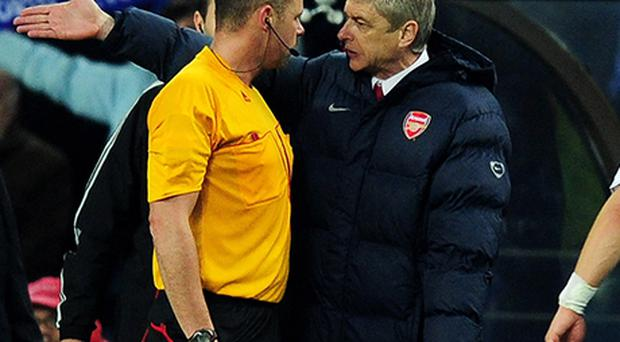Arsenal manager Arsene Wenger confronts referee Martin Hansson after Porto's second goal during last night's Champions League match. Photo: Getty Images