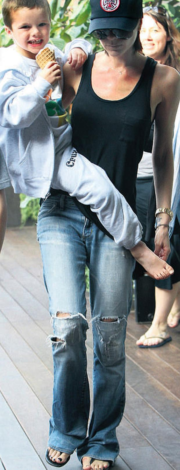Best foot forward: Bunions forced Victoria Beckham, pictured with son Cruz, to wear flip-flops after years of wearing heels
