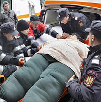 Victoria Lacatus is lifted by firefighters out of an ambulance in Bucharest, Romania (AP)