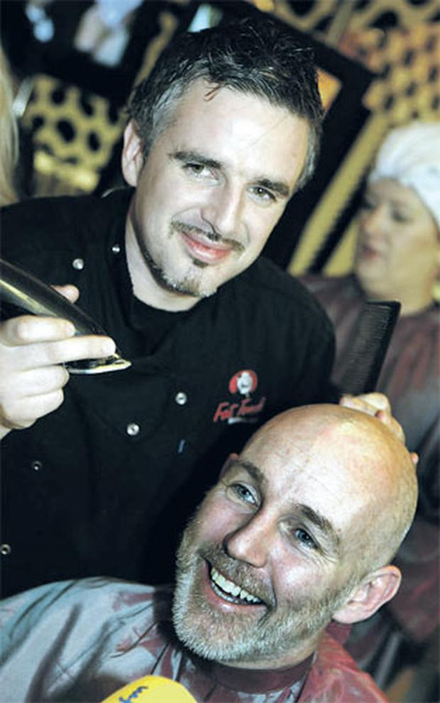 Ray D'Arcy laughing as his head is shaved by Galway barber John McGuire in Dublin yesterday.