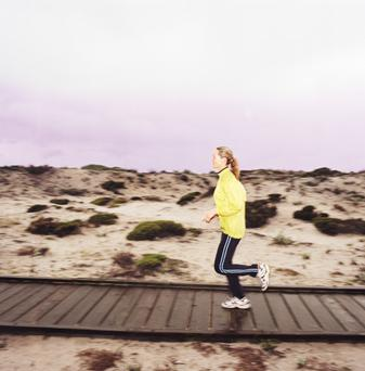 Mature woman jogging on boardwalk, side view (blurred motion)