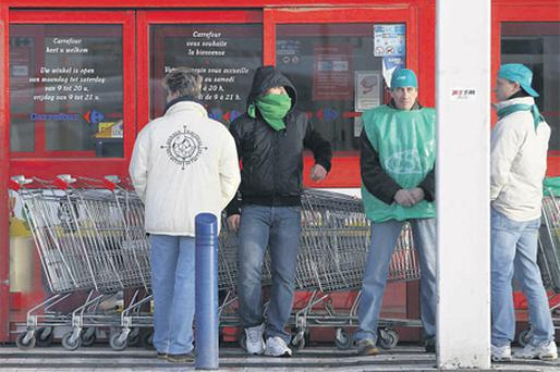Employees at Carrefour block the entrance of a store with shopping trolleys during a strike in Drogenbos, near Brussels, yesterday. Carrefour, the world's No. 2 retailer, said it would cut jobs and close stores in Belgium to restore profitability in the country amid intense competition from local rivals