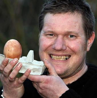 Mark Cornish, from Ipswich, Suffolk, poses with an over sized egg, laid by his hen