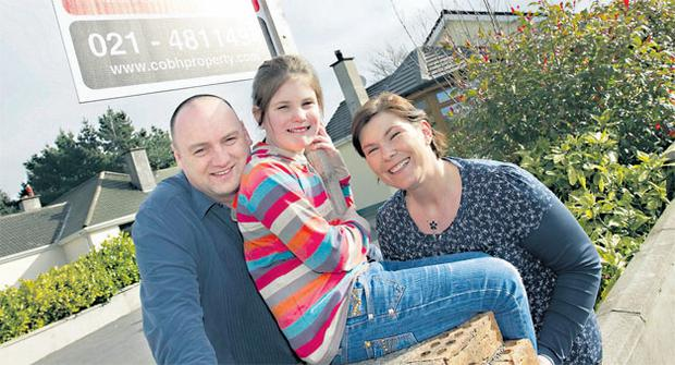 Uprooting: Moira and John Walsh with their daughter Caoimhe at their home in Cobh, Co Cork. The family are selling their home, which comes with a fully stocked vegetable garden, and emigrating to Canada.