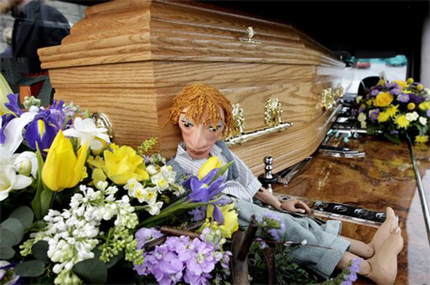 A puppet beside the coffin
