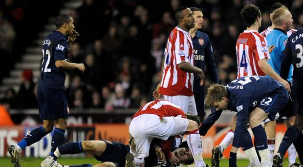 Stoke's Glenn Whelan comes to the aid of Aaron Ramsey, the stricken Arsenal player, who suffered a broken leg. Photo: Getty Images