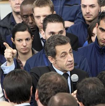 Nicolas Sarkozy (centre) speaks to workers at a Eurocopter plant in Marignane, southern France (AP)