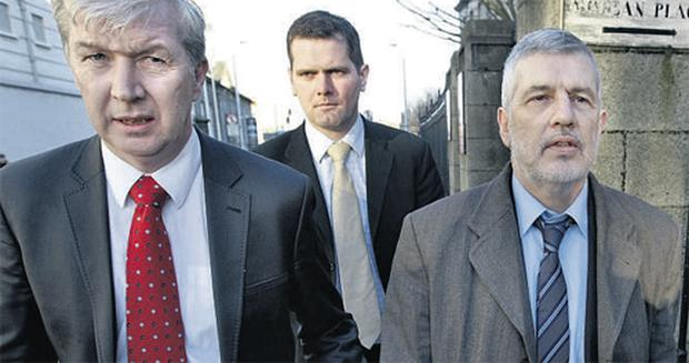 Liam Adams (right) leaving the Four Courts yesterday, accompanied by Det Sgt Jim Kirwin (left). Photo: Steve Humphreys