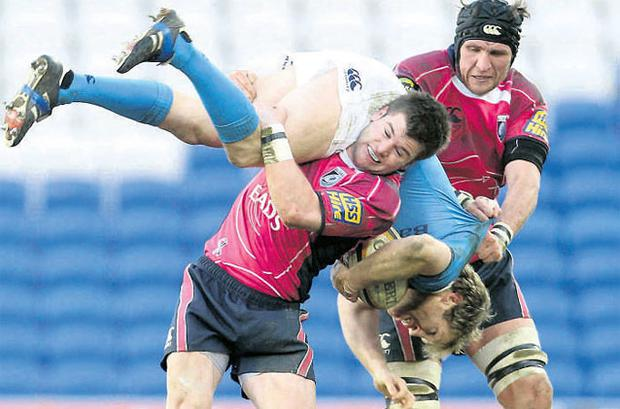 Leinster's Shaun Berne is upended by Ceri Sweeney, of Cardiff Blues, during yesterday's Magners League clash