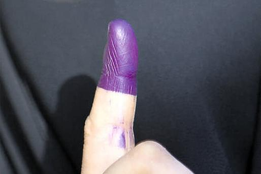 A veiled Iraqi woman displays her ink-stained index finger after casting her ballot at a voting centre in Baghdad's Sadr City yesterday