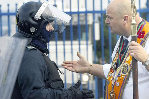A police officer confronts an Orange marcher. Contentious parades remain a major problem for the North's political leadership