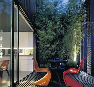 The balcony off the kitchen, with a table and Panton-style S chairs, is a convivial space.