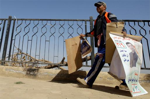 An Iraqi removes posters of candidates from a street in Baghdad yesterday after the election