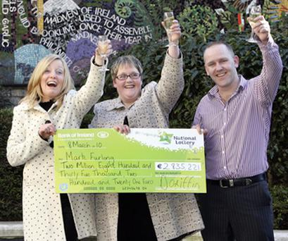 Mark Furlong and his partner Gillian Ryan (left) toast their good luck after collecting the cheque yesterday for his Lotto winnings, which he will share with his sister, Michelle Sinnott
