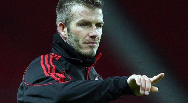 David Beckham gives instructions during AC Milan's training session at Old Trafford last night.