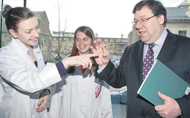 Taoiseach Brian Cowen at the Science Gallery, Dublin, yesterday, is shown a DNA sample bottle by Aisling Miller and Irene Mencke. Mr Cowen was at the Trinity College gallery to launch the government report on innovation. Photo: Frank McGrath