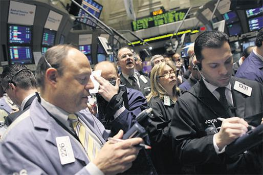 Traders work on the floor of the New York Stock Exchange. Stocks rose yesterday, with the Dow hitting a recovery high, as the Fed's renewed promise of low interest rates was underscored by a benign inflation reading