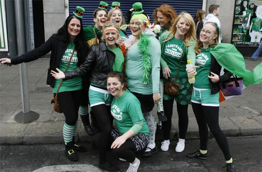 Brodie De Bono, Erin Moffatt, Sarah Mc Nulty, Sara Diem, Katherine Rance, Beth Ruttler, Michelle Des Jardins, Leah Maloney, and Kayla Poulios pose for photographs in their St Patrick's Day outfits during the parade in Dublin. Photo: Kyran O'Brien