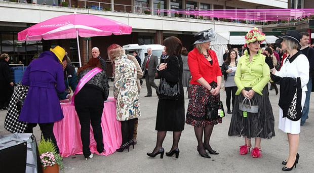 Hopefuls line up to register for the fashion contest during Ladies Day at Cheltenham. Photo: PA