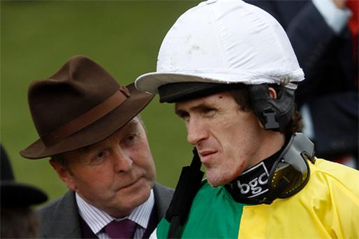 Tony McCoy (R) talks to racehorse trainer Jonjo O'Neill after two heavy falls at Cheltenham yesterday. Despite being shaken and sore McCoy will be fit to partner Denman in today's Gold Cup showpiece