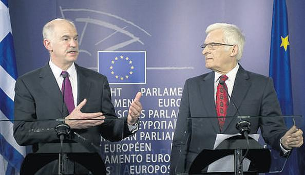 Jerzy Buzek, president of the European Parliament, right, listens as George Papandreou, Greece's prime minister, speaks during their press briefing at the European Union Parliament headquarters in Brussels yesterday