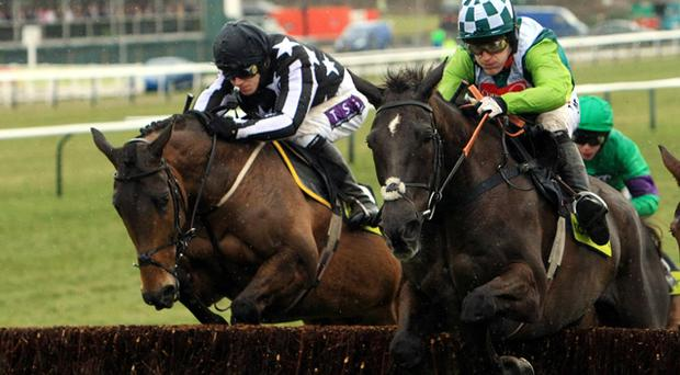 Gold Cup winner Imperial Commander ridden by Paddy Brennan (left) winner and second placed Denman ridden by Tony McCoy during the early stages of the race. Photo: PA