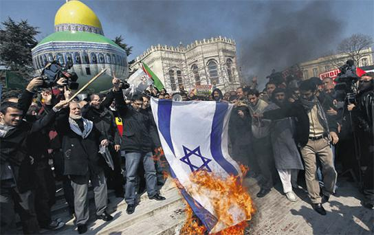 Demonstrators set fire to an Israeli flag during a protest against Israel in Istanbul yesterday