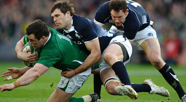 Cian Healy of Ireland is tackled by Sean Lamont and Graeme Morrison