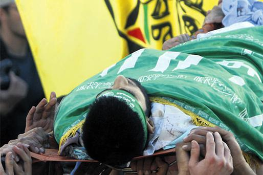 Palestinians carry the body of Mohammed Qadus during his funeral in the West Bank yesterday