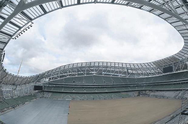 Workers apply the finishing touches to the newly seeded pitch at the new home of Irish rugby and soccer, the Aviva Stadium at Lansdowne Road, Dublin.