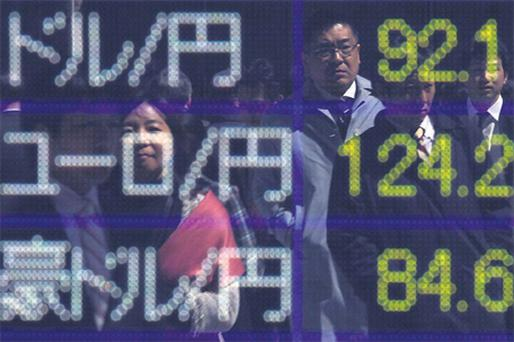 Pedestrians are reflected in an electronic board displaying the Japanese yen's exchange rate against the US dollar, euro and the Australian dollar, outside a brokerage in Tokyo yesterday
