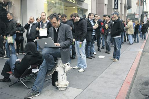 Customers wait in line to purchase an iPad during a launch event at the Apple retail store in San Francisco, California, on Saturday