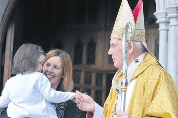 Cardinal Sean Brady greets Sharon Watters and her daughter Jessica, who receives a blessing, after Easter Sunday Mass at St Patrick's Cathedral in Armagh