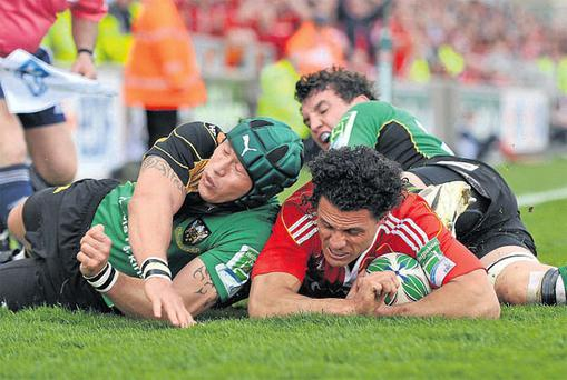 Munster's Doug Howlett scores his side's second try despite the efforts of Bruce Reihana, left, and Phil Dowson of Northampton Saints. Photo: Diarmuid Greene