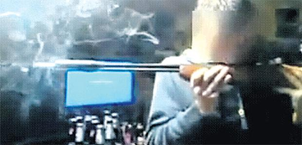 A still from the video posted on YouTube which shows a youth smoking cannabis from a rifle