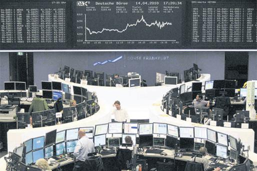 Traders are pictured at their desks in front of the DAX board at the Frankfurt stock exchange yesterday