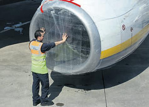 An aircraft maintenance worker covers a jet engine intake on a Ryanair plane with cling film at Belfast City Airport yesterday
