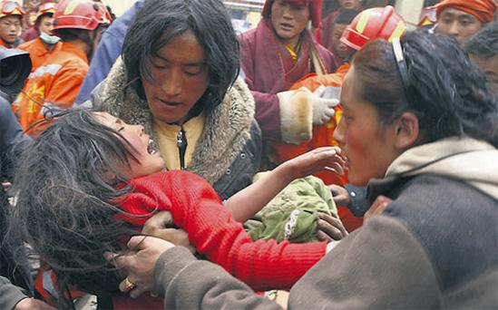 Rescuers comfort a 13-year-old girl who had been trapped for 50 hours in a hotel in Yushu, Qinghai province, China