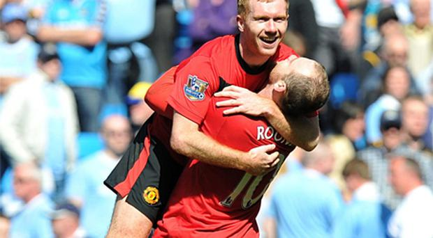 Paul Scholes and Wayne Rooney celebrate after Scholes' injury-time goal gave Manchester United a dramatic victory in the Manchester derby yesterday