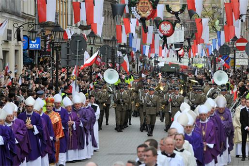 Catholic clergy and a military band take part in a funeral procession in Krakow