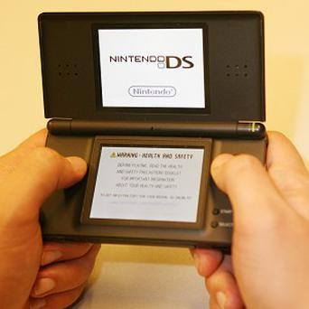 A man plays a game on a Nintendo DS console